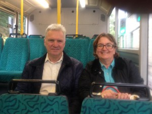 Councillor Janet Battye and Michael Smith sat on board a bus smiling